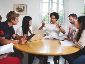 Studenten vieler Nationen sitzen um einen Tisch herum.