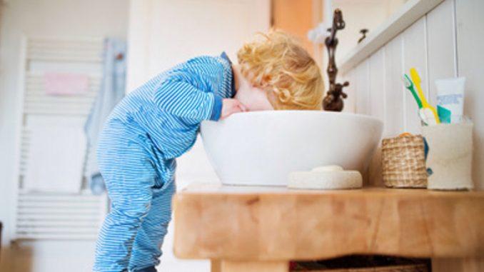 Schwedisches Kind am Waschbecken.