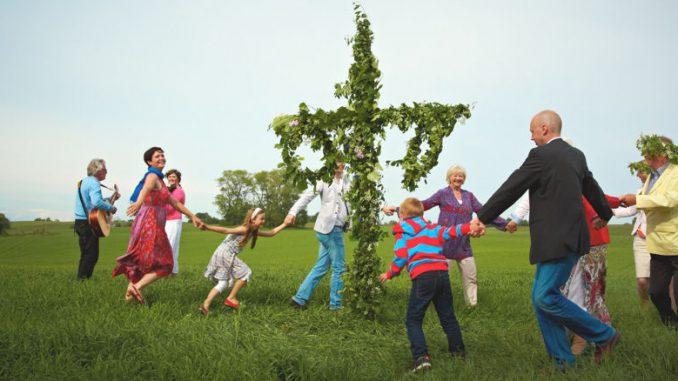 Eine Familie tanzt in Schweden um die Midsommarstange.
