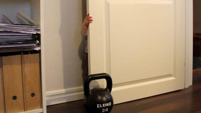Kleinkind versteckt sich hinter einer Tür