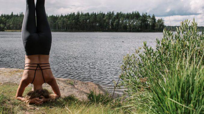 Eine Frau beim Yoga: Kopfstand vor dem schwedischen See.