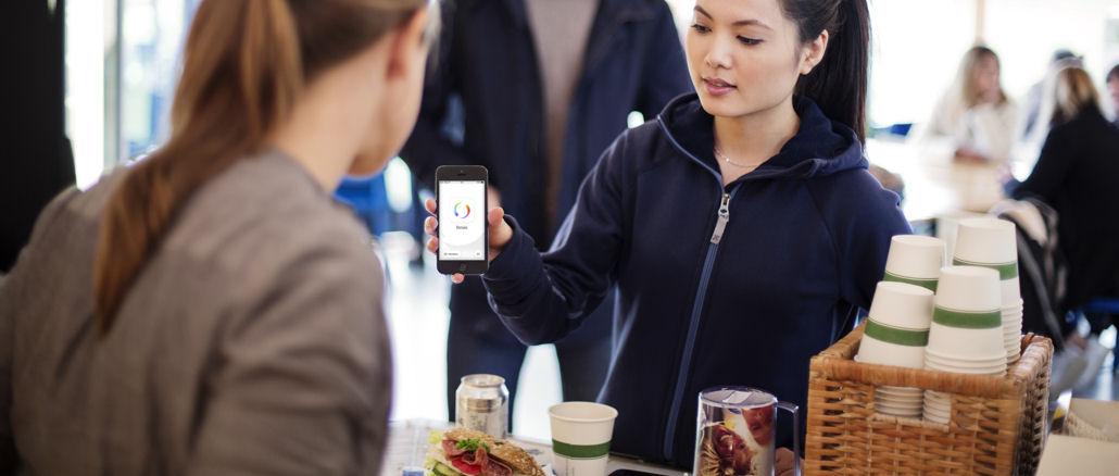 Eine Frau bezahlt in einem Café mit Swish.